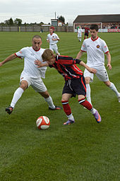 F.C. United players challenge a Mickleover Sports player for possession of the ball while a crowd of supporters watch from the far end of the pitch near the Mickleover goal.
