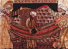 Enluminure islamique représentant trois personnes portant des djellabas et des turbans de chaque coté d'un drap décoré. Les deux personnages situés le plus au fond soulèvent une étoffe noire révélant un mur de briques avec une porte fermée. Un septième personnage portant la même tenue se trouve au centre et tient une pierre circulaire noire se trouvant au milieu du drap tendu.
