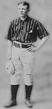 A baseball player standing, facing slightly to his right, with his right arm relaxed and holding a baseball cap, and his left arm raised so that his left hand his resting on his hip