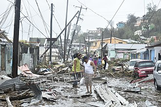 Hurricane Maria - A road in the Roseau area is littered with structural debris, damaged vegetation and downed power poles and lines.