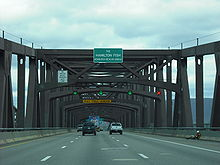 "A roadway with large brown metal latticework above it. On the side facing the camera is a small white on green sign reading ""The Hamilton Fish Newburgh-Beacon Bridge"""