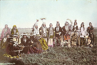 Confederated Tribes of Siletz Indians - Many Native Americans gather around a drum, preparing for a powwow in 1900