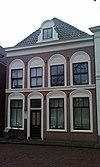 Pand, met voorgevel, voorzien van vensters in rondboognissen, geprofileerde puibalk en houten kroonlijst