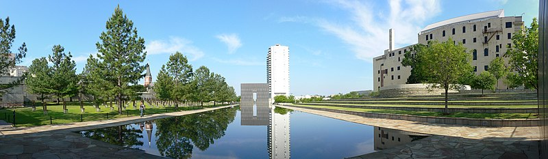 "A panoramic view of the memorial. In the center is a large stone structure shaped as a gate with ""9:03"" at the top. At the center of the gate is a large hole and through it a road can be seen. The Regency Towers building is visible on the right of the image in the background. The gate is reflecting in a pool of water in front of it, and grass and trees are visible to the left and right of the pool."