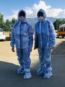 Dwóch sanitariuszy ubranych w fartuchy medyczne na zewnątrz.