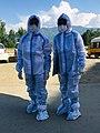 To paramedikere iført medicinske PPE -kjoler udendørs.