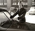 Parkeringsvakt i vinterkläder fäster böteslapp på felparkerad bil - Nordiska museet - NMA.0030982.jpg
