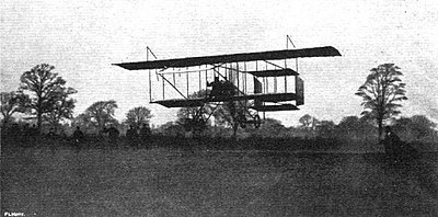 monochrome photograph of a biplane flying low over a field
