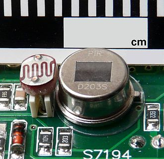 Motion detector - A passive infrared detector mounted on circuit board (right), along with photoresistive detector for visible light (left). This is the type most commonly encountered in household motion sensing devices and is designed to turn on a light only when motion is detected and when the surrounding environment is sufficiently dark.
