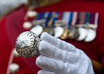 Pictured is a Grenadier Guardsman wearing his Red Tunic and holding a Regimental Cane. MOD 45159558.jpg
