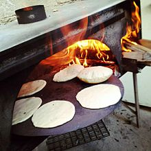 Six pitas baking on a circular pan in a wood-fired oven