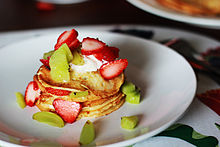 Pancake decorati con uva, fragole e panna