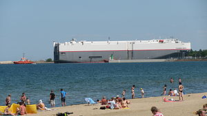 Port of Gdańsk - Car carrier in the entrance to the inner port, as seen from the nearby beach.