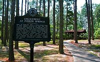 "Historic marker reading ""Engagement at Poison Springs"" in foreground of a forested area with rustic wooden pavilion in the background."