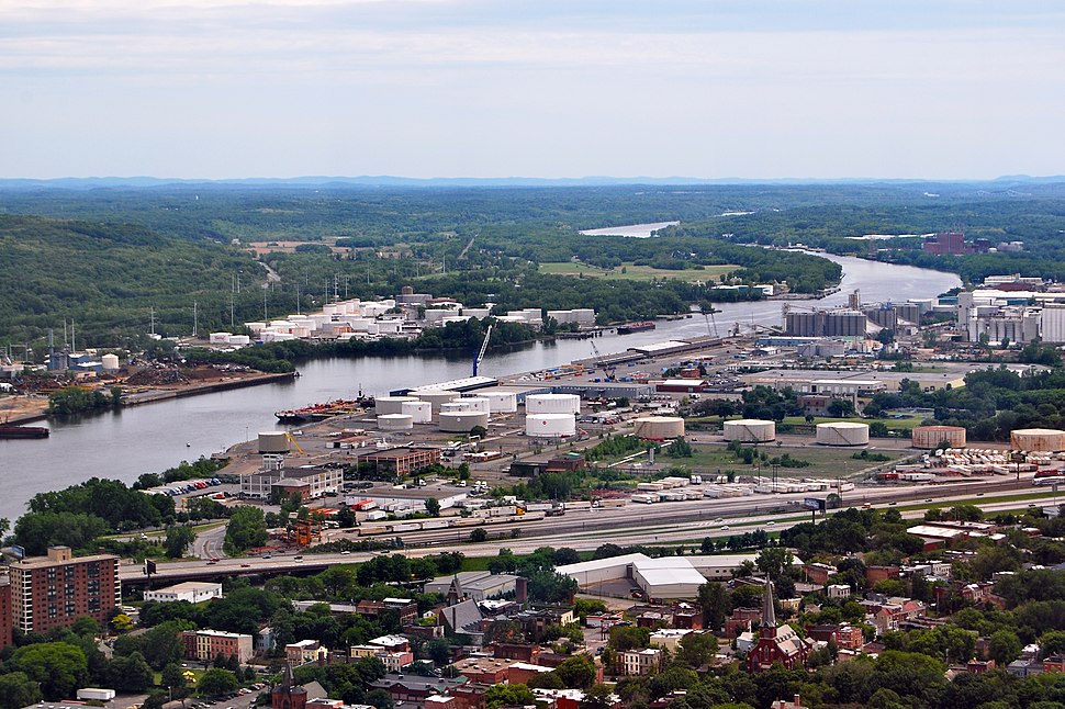 Aerial view of an industrial zone; large silos, cranes, storage tanks, and a highway are seen.