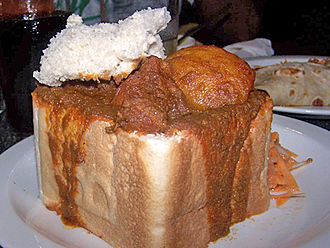 An example of bunny chow served in Durban, originated in the Indian South African community Quarter Mutton Bunny Chow.jpg