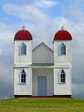 Einfaches weißes Gebäude mit zwei roten Kuppeltürmen