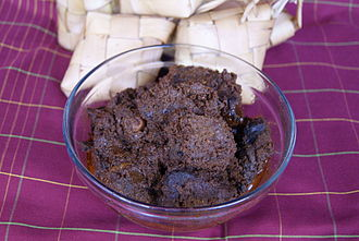 Rendang - Authentic Minangkabau rendang is dark in colour, served with ketupat