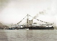 A photograph showing a steamship in port, fully dressed with flags and a single visible gun turret towards the bow