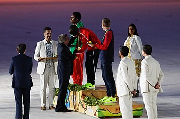 Eliud Kipchoge at the top of the podium during the 2016 Summer Olympics in Rio de Janeiro, Brazil. He is seen during the medal ceremony with the gold medal for his win in the men's marathon.