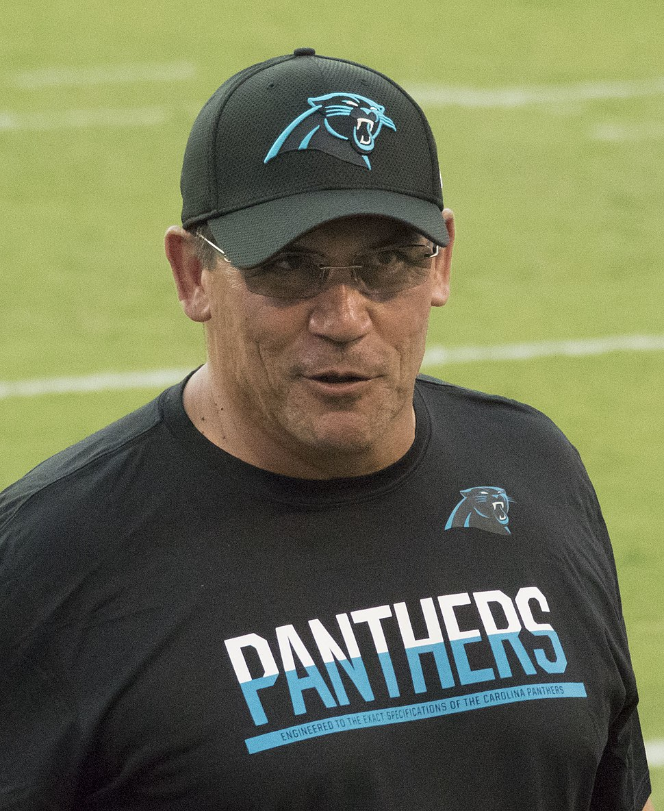 Color head-and-torso photograph of dark-haired Hispanic man (Ron Rivera), wearing a white and sky blue sport shirt and rectangular eyeglasses, seated at a press conference table with another man.