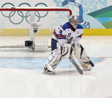 "An ice hockey goaltender is on the ice in front of his net. He is wearing a white sweater with the letters ""USA"" on the front in blue."