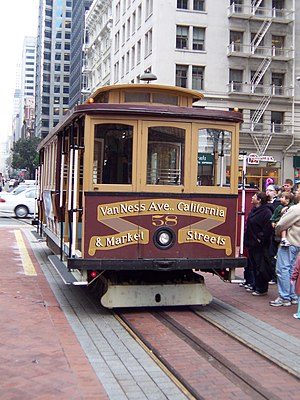"A cable car with the words ""Van Ness Avenue, California, and Market Streets"" on the front is stopped next to people who are about to get on."