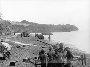 Soldiers wearing steel helmets on a beach, manning an antiaircraft gun. In the background are jeeps and trucks, and an LST.