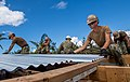 Seabees apply metal roofing sheets while reconstructing. (44604813675).jpg