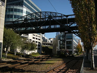 Central Waterfront, Seattle - Part of the Bell Street Bridge, spanning railroad and trolley tracks. To the right, the footbridge continues across Alaskan Way to Pier 66. The 2006 Department of Neighborhoods definition includes all of this in the Central Waterfront; other definitions exclude it or are ambiguous about the matter.