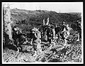 Soldiers on the move, France, during World War I. The stripped and scarred landscape is depicted in the background. Along the front of the photograph six soldiers are walking, fully equipped and laden (4688014831).jpg