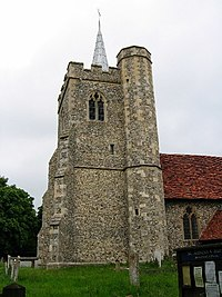 A flint tower with a battlemented parapet and a small spire; to the right is a stair turret rising higher than the tower