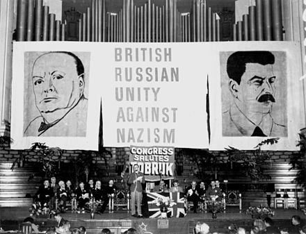 Huge portraits of Churchill and Stalin, Brisbane, Australia, 31 October 1941 StateLibQld 2 108020 Guests seated on stage in front of a backdrop of giant posters at the Aid to Soviet Congress, Brisbane City Hall, October 1941.jpg