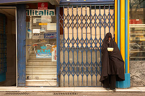Woman begging on the street in Tehran, holding...