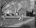 T-SHAPED FRAME HOUSE WITH ROOFED PORCHES. A POST ROCK FENCING IS IN THE FORGROUND - Town of Munjor, Munjor, Ellis County, KS HABS KANS,26-MUNJ,1-3.tif