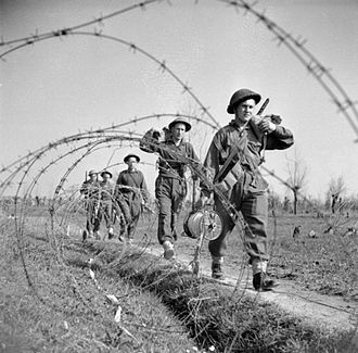 London Irish Rifles - Infantrymen of the 2nd Battalion, London Irish Rifles move forward through barbed wire defences on their way to attack a German strongpoint on the southern bank of the River Senio, Italy, 22 March 1945.