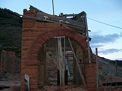 a mostly destroyed building with a sandstone arch entrance still standing. The arch is being propped up with wood to prevent its collapse. Above the doorway is a wooden sign that reads Thistle; some letters have fallen off.