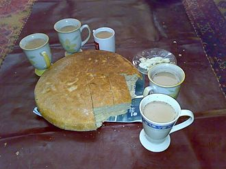Chitrali cuisine - A loaf of tikki bread served with milk tea.