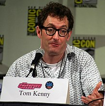Tom Kenny seated at a microphone looking off to his left