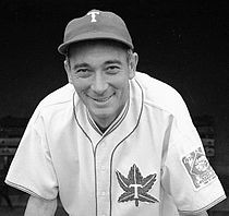 "A man, wearing a baseball cap with a ""T"" in the center and a white baseball uniform with the Toronto Maple Leafs baseball logo on the left breast, leans forward smiling."