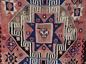 Kilim motifs - Detail of a Turkish kilim, illustrating usage of several motifs including Eye, Hook, and Star. The central gul (octagonal medallion) consists of a (stepped) dragon or scorpion motif around a large star.