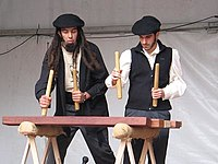 Two txalaparta players at a performance in a fiesta.jpg