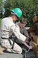 U.S. Marine Corps Lance Cpl. Ryan E. Brake, left, and Cpl. Nathaniel Fetner, both with the 9th Engineer Support Battalion, secure a rope for an anchor point in their safety harness during renovation work 130721-M-DR618-006.jpg