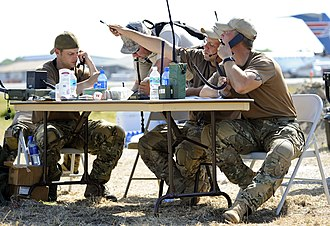 United States Air Force Combat Control Team - Combat Controllers directing air traffic from a card table at Toussaint Louverture International Airport in Port-au-Prince.