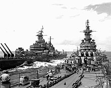 Two large battleships sailing toward the viewer. Personnel can be seen on the decks of both ships.