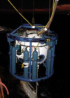 Night view of a white spherical pressure chamber in a blue pipe frame supporting several blue bulk gas storage clinders, suspended over the water by cables. The bell umbilical is visible at the top and a ballast weight can be seen below at the water surface