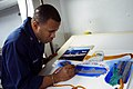 US Navy 021231-N-9867P-021 Draftsman 2nd Class Ernie Dwight works on an assignment in the ship's photo lab.jpg