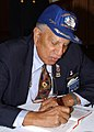 US Navy 030207-N-8894M-008 1st LT William B. Ellis, a Tuskegee Airmen in World War II assigned to the Fighting 99th, 332nd Fighter Wing, signs an autograph during an African American History month breakfast.jpg