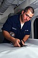 US Navy 040814-N-1513W-015 Aircrew Survival Equipmentman Airman Ronald Peeples of Houston, Texas, cuts a piece of vinyl to the exact size needed for a dust cover in the paraloft shop aboard the aircraft carrier USS John C. Sten.jpg
