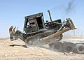 US Navy 050601-N-4958O-007 A Seabee assigned to the Naval Mobile Construction Battalion Two Four (NMBC-24) offloads a bulldozer at Camp Hit.jpg
